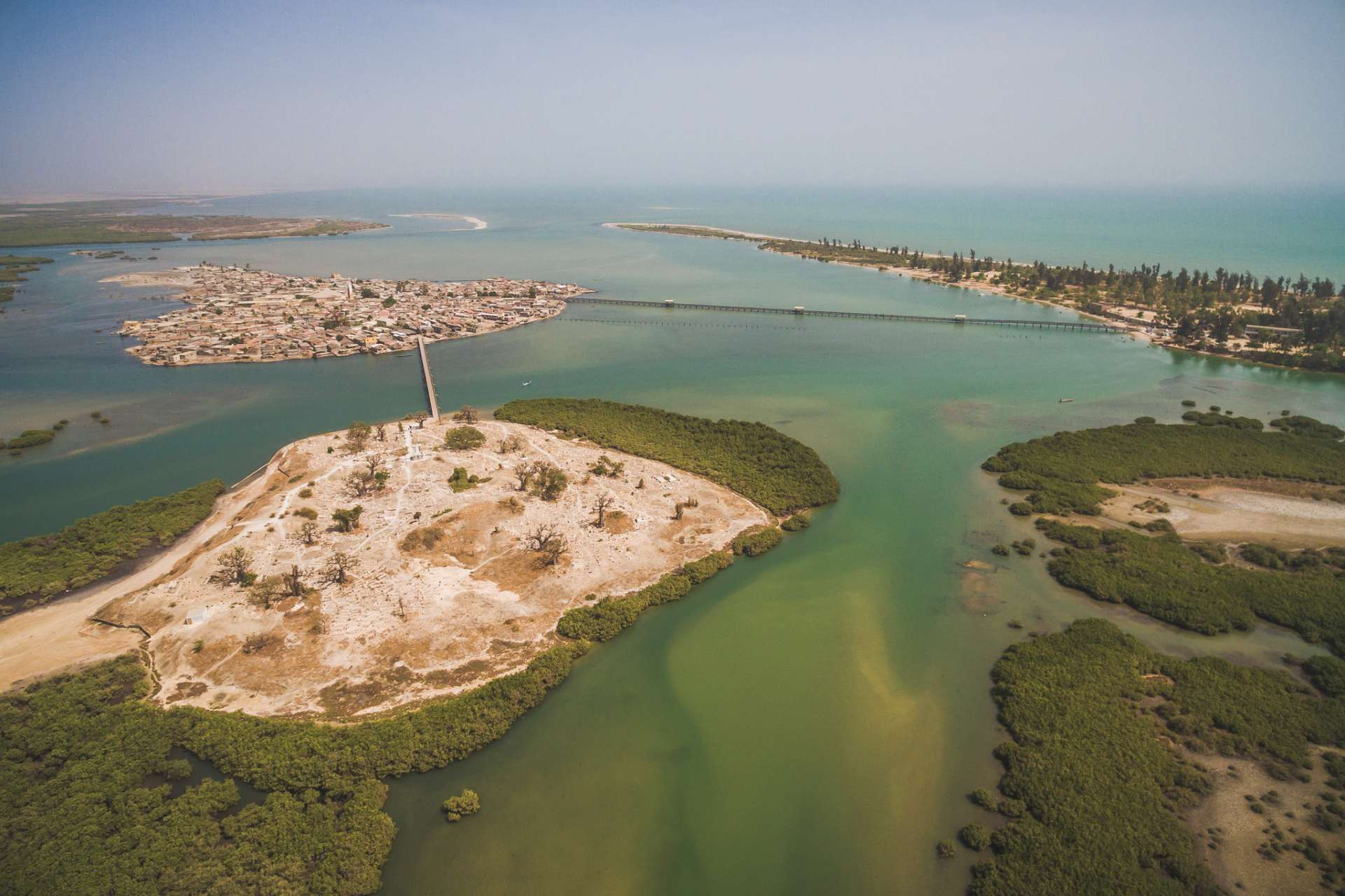 Joal se trouve sur le continent et Fadhiout sur une île artificielle constituée d'amoncellements de coquillage et reliée à la côte par un pont en bois qui enjambe la mangrove.